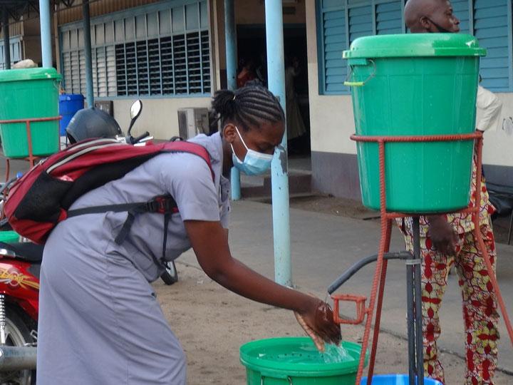 Une élève se lave les mains au Cours Secondaire Notre Dame de Cotonou